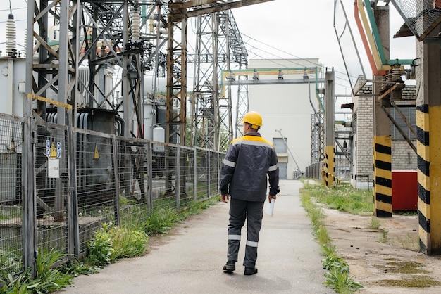Инженер совершает экскурсию и осмотр современной электрической подстанции. энергия. промышленность.