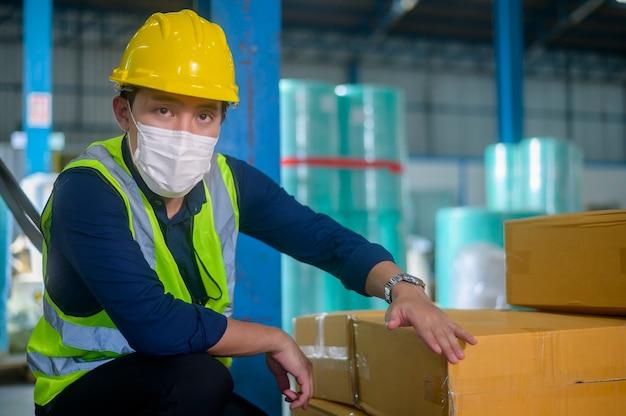 Инженер в медицинской маске, защитный шлем, работает на складе завода