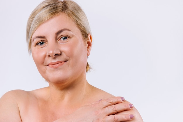 サイドスペースのある白い背景に甘い笑顔と純粋な自然な肌を持つ年上の女性の拡大写真。高品質の写真