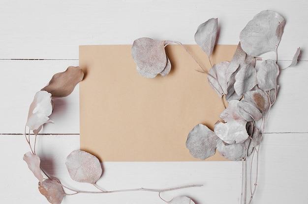 装飾的なユーカリと白い木の板の封筒