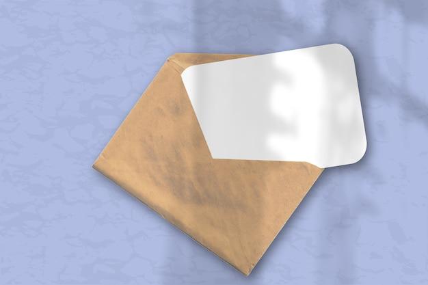 Конверт с листом фактурной белой бумаги на нежно-синем фоне стола. естественный свет отбрасывает тени из окна. горизонтальная ориентация.