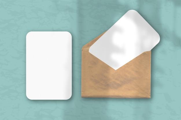 Конверт с двумя листами фактурной белой бумаги на сине-зеленом фоне стола, естественный свет отбрасывает тени из окна. горизонтальная ориентация.