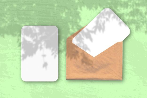 Конверт с двумя листами фактурной белой бумаги на зеленом столе