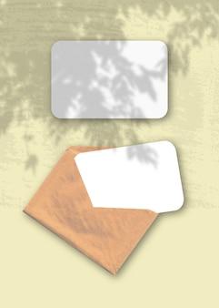 黄色の背景に2枚の織り目加工の白い紙が入った封筒モックアップオーバーレイと植物の影