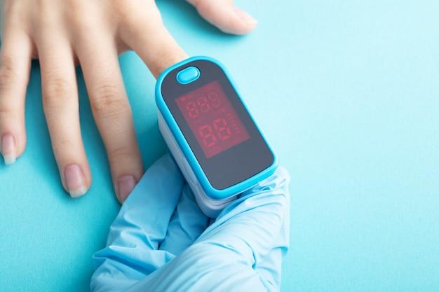 青の背景に女性の手の低酸素症に不可欠な医療機器