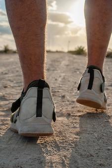 Вечерняя прогулка. мужчина идет по песчаной дороге на пляже вечером во время заката.