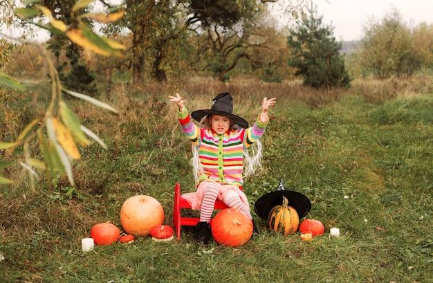 사악한 소녀가 큰 마법사 모자를 쓴 크고 작은 호박 사이에 풀밭에 앉아 있고