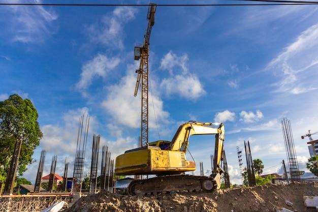 Экскаватор погрузчик машина на строительной площадке с краном и стальных стержней. вид сзади.
