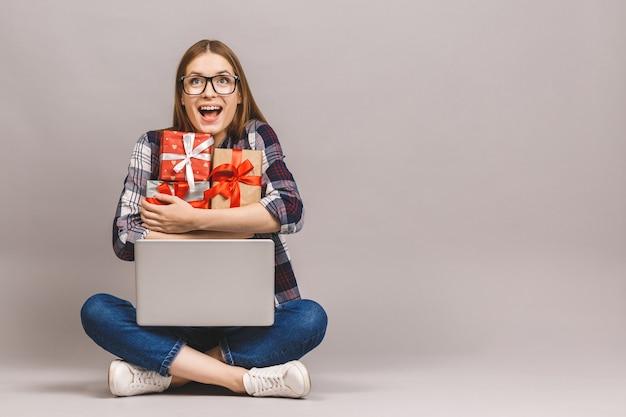 Взволнованная случайная девочка, держащая ноутбук, сидя на полу со стеком подарочных коробок