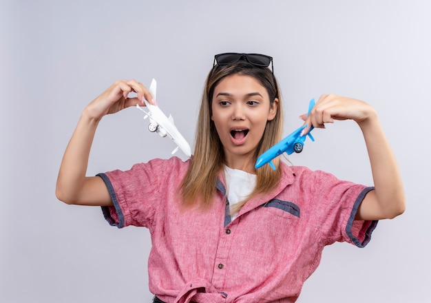 サングラスをかけた赤いシャツを着て、白と青のおもちゃの飛行機を飛ばしながら驚くほど見ている興奮した素敵な若い女性