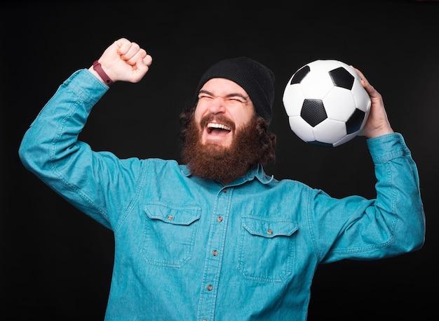 Возбужденный молодой бородатый мужчина держит футбольный мяч и кричит от победы возле черной стены.