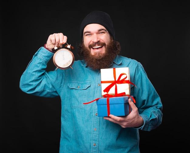 흥분된 젊은 수염 난 남자가 선물과 작은 시계를 들고 시간이 다가오고 있음을 보여줍니다.