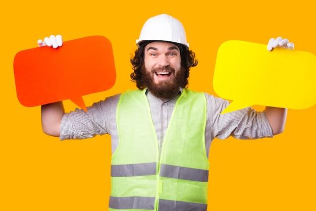 Взволнованный молодой инженер смотрит в камеру и держит два речевых пузыря возле желтой стены