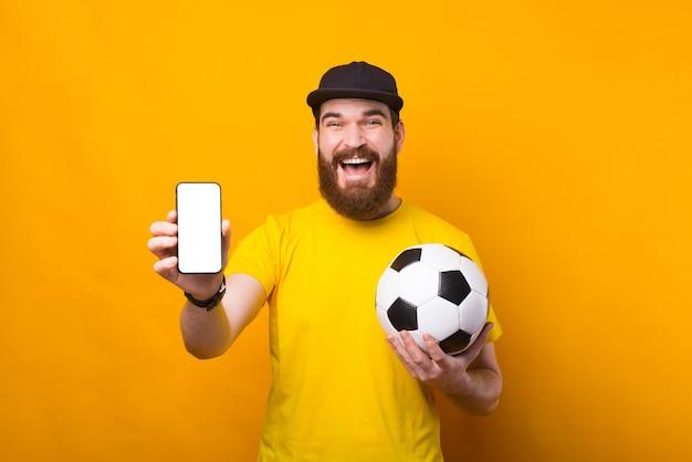 Взволнованный молодой человек держит футбольный мяч и улыбается по телефону