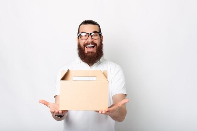 배달 상자를 가진 흥분된 젊은 남자가 흰 벽 근처의 카메라에 놀랍게 웃고 있습니다.