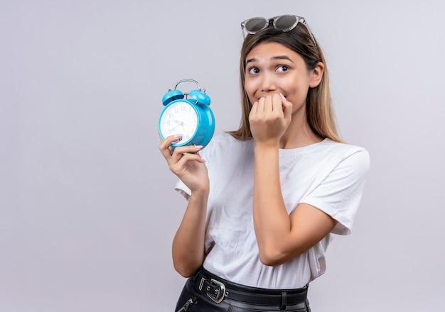 あごに手で青い目覚まし時計を保持しているサングラスの白いtシャツの興奮した若い女性