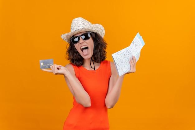 地図とクレジットカードを保持している太陽の帽子とサングラスを身に着けているオレンジ色のシャツを着た短い髪の興奮した若い女性