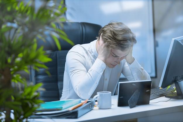 Обессиленный человек на рабочем месте после тяжелого рабочего дня, уставший от рутины.