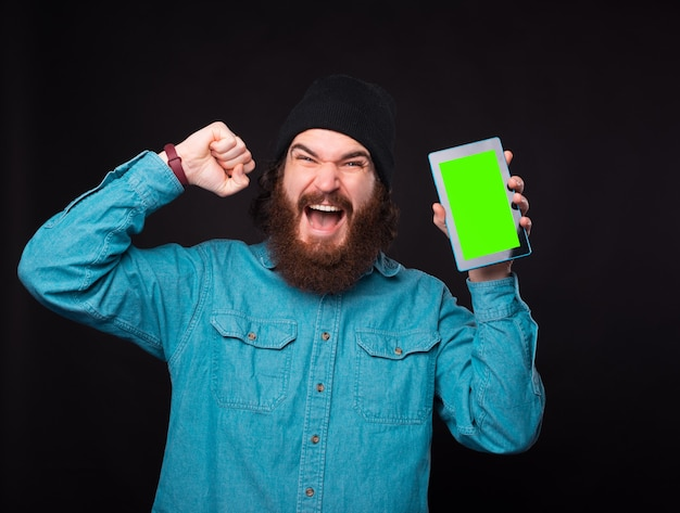 Exicted 젊은 수염 난 남자가 카메라를보고 녹색 화면이있는 태블릿을 들고있다