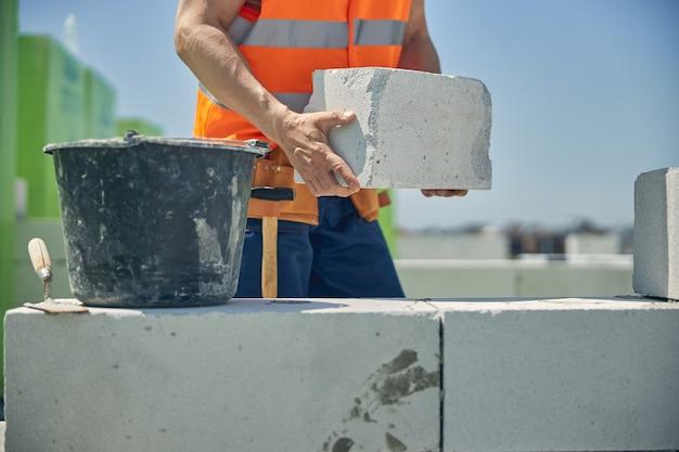 Опытный кавказский каменщик в светоотражающем жилете кладет кирпичи снаружи