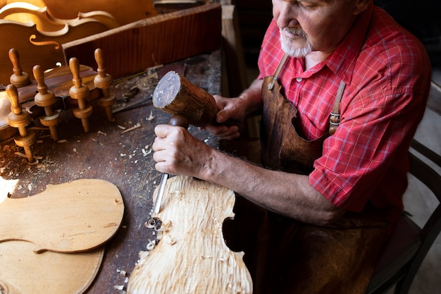 목공 워크숍에서 자신의 프로젝트를 진행하는 경험 많은 회색 머리의 수석 남자 목수