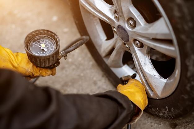 주황색 장갑을 착용 한 숙련 된 정비사가 자동차 바퀴에 공기 밸브를 놓고 압력을 가할 준비를하고 있습니다.