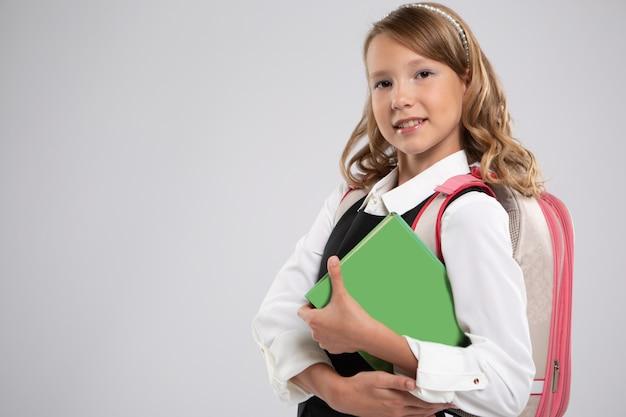 スクールバッグと本と笑顔の美しい若い女子高生の表情豊かな肖像画。