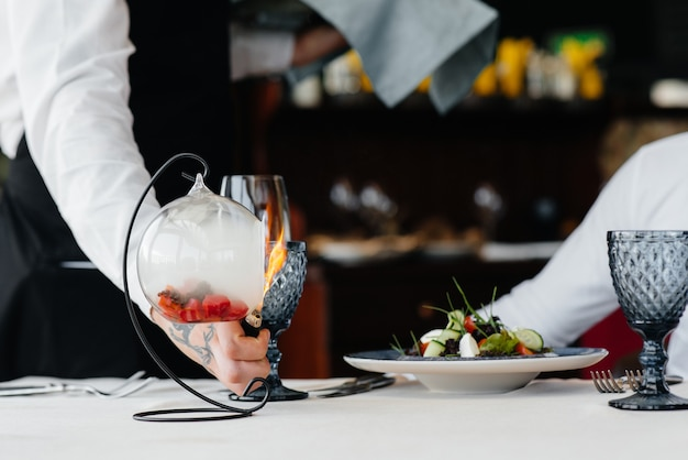Изысканный салат из морепродуктов, тунца и черной икры в красивом горении с огнем подается на стол в ресторане. изысканные деликатесы высокой кухни крупным планом.