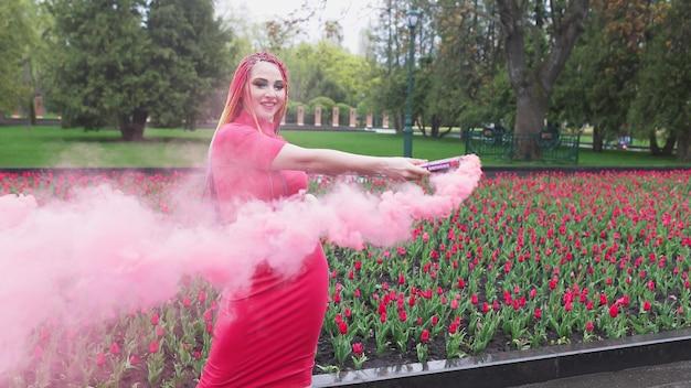 Неординарная девушка в красном платье с макияжем и разноцветными косичками. симпатичная улыбка и позирование в густом розовом дыму в парке под дождем