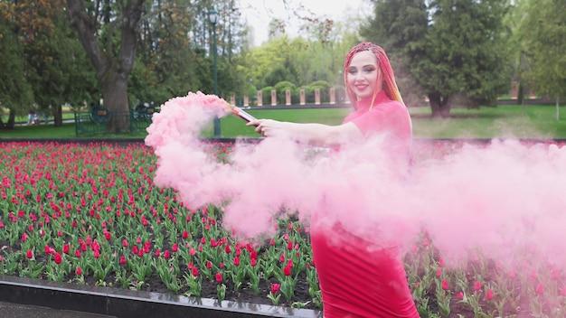 Неординарная девушка в красном платье с макияжем и разноцветными косичками. симпатичная улыбка и позирует в густом розовом дыму в парке под дождем