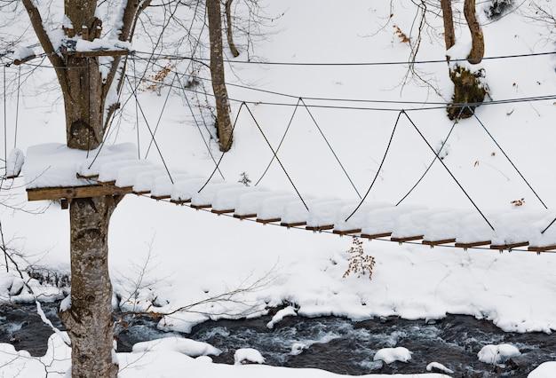 冬の無人のカルパティアの森の崩れかけた木々に、真っ白な雪に覆われた極端なロープパークがあります。