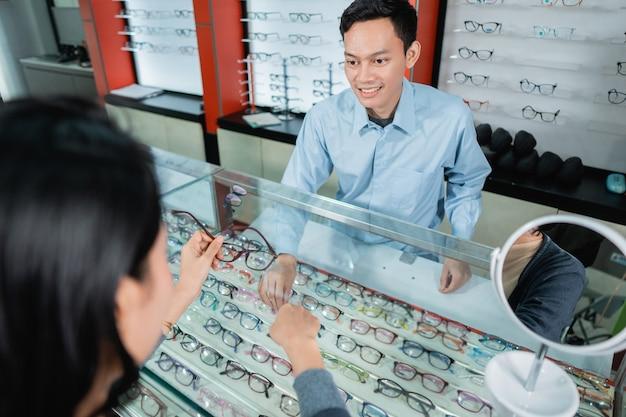 안과 진료소 직원이 안과 진료소에서 사용할 안경을 선택할 때 여성 소비자에게 서비스를 제공하고 있습니다.
