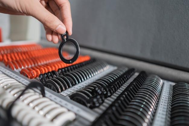 Рука офтальмолога берет калибр линз для тестовых очков в коробке с набором линз в офтальмологической клинике.