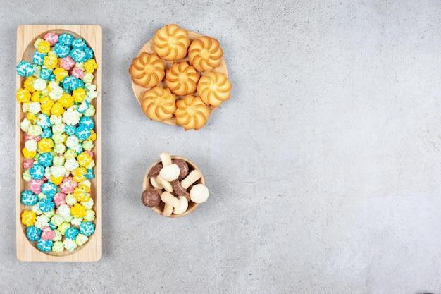 Ароматная сервировка конфет из попкорна, печенья и шоколадных грибов на мраморном фоне. фото высокого качества