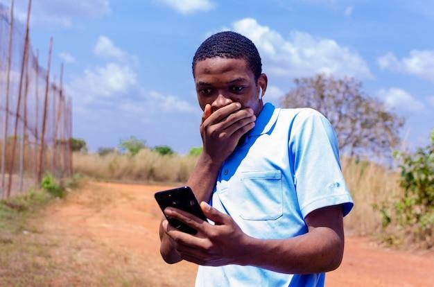ハンサムなアフリカの少年は、彼が彼の携帯電話で見た新しいことに驚きました