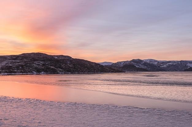 氷に覆われた山の湖。湖の北の山に沈む魔法のマゼンタの夕日。コラ半島。