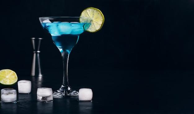 얼음 블루 라군 칵테일이 라임 조각으로 장식 된 칵테일 잔에 서 있습니다.