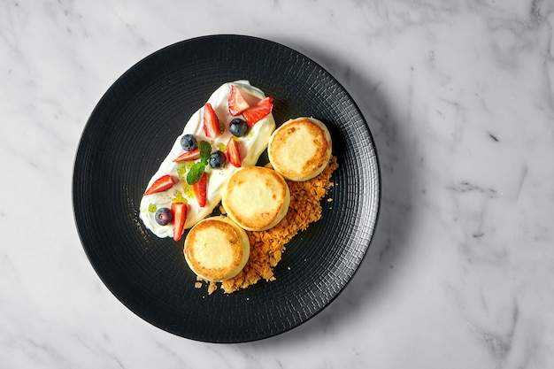 Идеальный завтрак - творожные оладьи с белым соусом, ягодами, клубникой и хрустом в черной тарелке на мраморной поверхности.