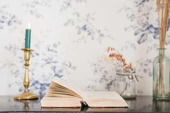 An illuminated candle and book on desk against wallpaper