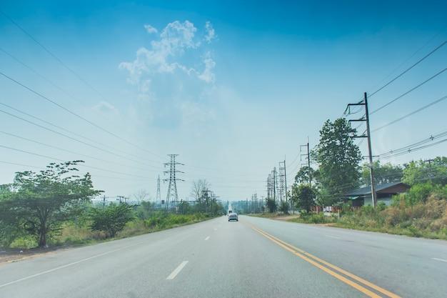 空と雲を背景に、道に沿って木々や街灯柱がある、開いた道路をクルージングしている車の画像。