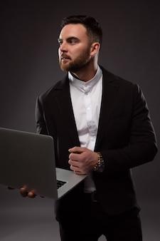 手に持っているラップトップで作業している、集中力のある残忍なビジネスマンの画像。