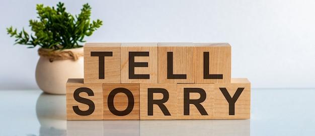 Изображение букв, отпечатанных на деревянных блоках со словами - сказать извините. концепции вид спереди, цветок на заднем плане.