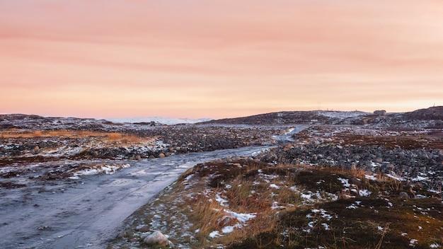 Непроходимая обледенелая дорога через зимнюю тундру. неровная каменистая дорога уходила вдаль. кольский полуостров.