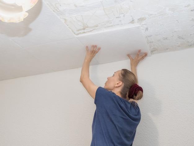 独立した女性が天井のパネルを接着する