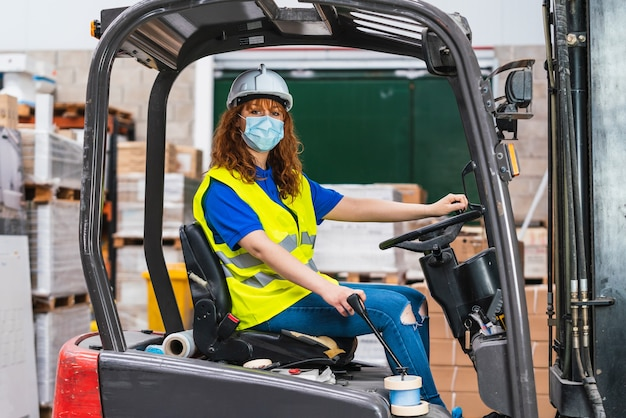 창고에서 지게차를 사용하여 의료 마스크를 쓰고 산업 여성 노동자