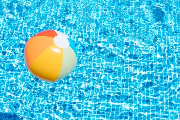 Надувной мяч на фоне воды в бассейне концепция лета и путешествия копией пространства