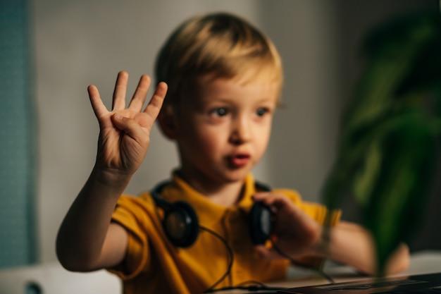 호기심 많은 소년이 온라인 수업을 주의 깊게 듣고 모니터에 숫자 4를 보여줍니다.