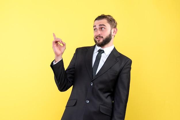 Неуверенный молодой человек в костюме и галстуке поверх желтого