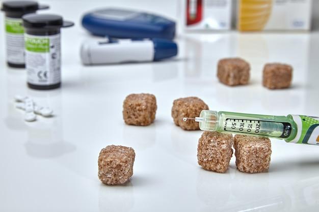 針にインスリンを一滴垂らしたインスリンペン、血糖値計、テストストリップ、白い医療テーブルに砂糖の塊を入れた杖。糖尿病管理の概念