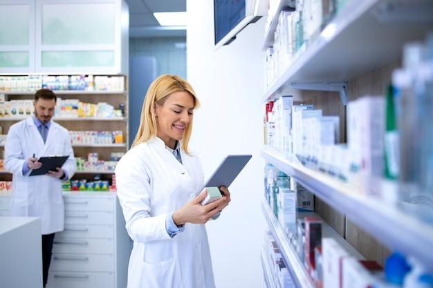 Умная женщина-фармацевт проверяет новую спецификацию лекарств онлайн в аптеке.